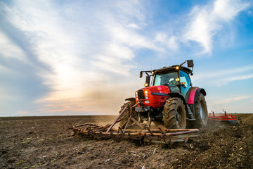 Fotomurales - Tractor cultivating field at spring