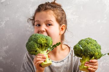 Little beautiful girl eating broccoli. Healthy vegan baby foods.