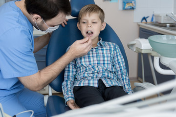 Portrait of dentist examining teeth of little boy sitting in dental chair visiting modern dentistry clinic