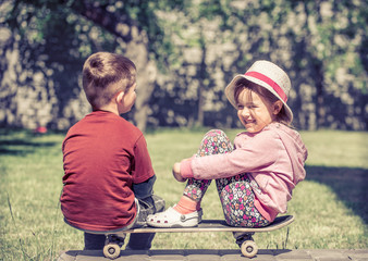 little girl and boy playing on skateboard, against the backdrop of a green garden, concept of childhood friendship