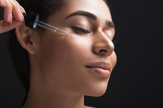 Youthfulness concept. Close up of pleased female expression with closed eyes. Woman applying serum oil on facial skin. Isolated on black background
