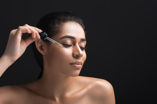 Skin care concept. Portrait of beautiful lady receiving serum oil treatment. Copy space in right side. Isolated on black background