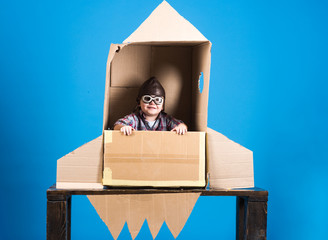 Kid in helmet and pilot glasses sit in cardboard rocket. Childhood concept - happy boy play astronaut. Cosmonaut concept - child with hand made toy rocket playing and dreaming of becoming spacemen.