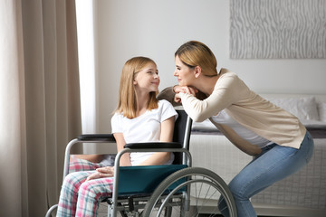 Young woman taking care of teenage girl in wheelchair indoors