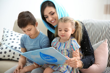 Muslim woman reading book to her children at home