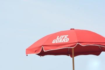 Red life guard umbrella on the beach