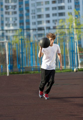 cute young sporty boy in white t shirt plays basketball on his free time, holidays, summer day. Sport  health lifestyle concept