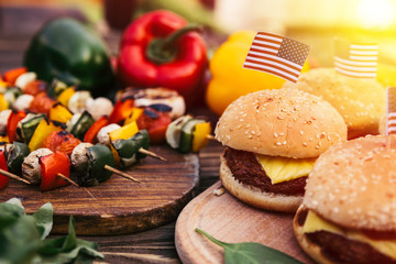 Burgers with us flags cooked outdoors on grill