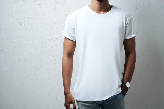 Guy wearing white blank t-shirt, grunge wall, horizontal studio close-up