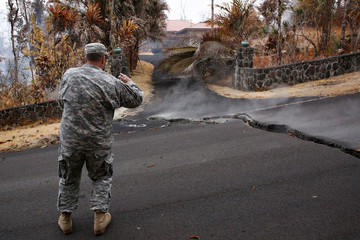 Major Jeff Hickman, of the Hawaii National Guard, takes a photo in the Leilani Estates subdivision during ongoing eruptions of the Kilauea Volcano
