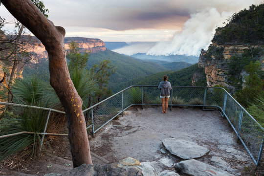 Girl at a bushwalking lookout with a view over a remote bushfire and smoke in the Blue Mountains, New South Wales, Australia.