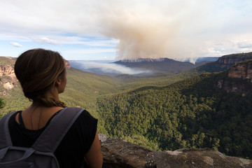 A female hiker stops to look at an impending bushfire from a high vantage point in the Blue Mountains National Park, Australia.