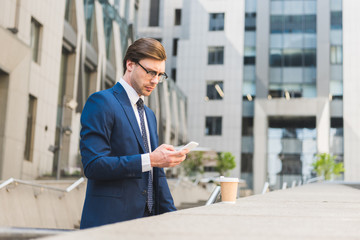 attractive young businessman in stylish suit with paper cup of coffee using smartphone near business building