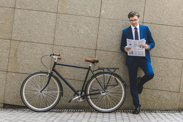 handsome young businessman in stylish suit with bicycle reading newspaper leaning on wall