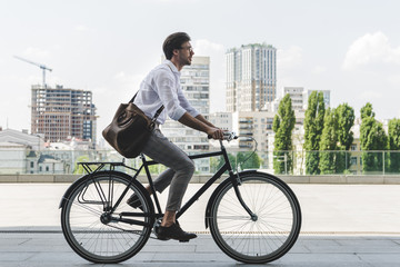 side view of young man in stylish clothes riding vintage bicycle on city street