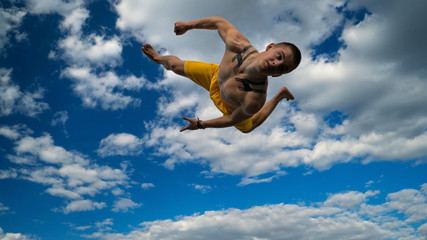 Tricking on street. Martial arts. Man performs somersault ahead barefoot. Shooted from bottom foreshortening against sky.