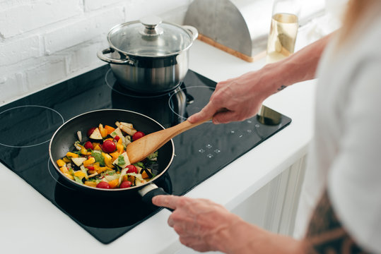 cropped shot of man cooking vegetables in frying pan on electric stove