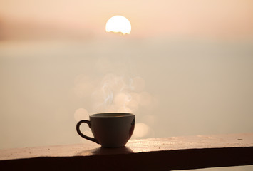cup of coffee with sunset or sunrise background