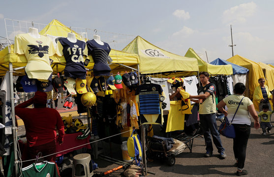 Domestic football teams' shirts, caps and other items with logos of Club America are displayed for sale outside the Azteca stadium of Mexican First Division in Mexico City