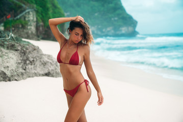 Portrait of a gorgeous woman in a red bikini on the beach with white sand. Beautiful girl with a sexy tanned body on a summer vacation near the ocean. Model blonde with curly hair is posing.