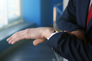 businessman looking at his watch on his hand, watching the time