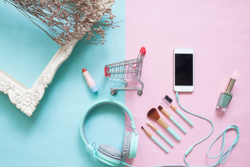 Creative flat lay shopping cart with smartphones and beauty items on pastel color background, Beauty and cosmetic, Online shopping
