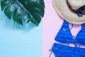 Top view summer concept, Monstera leaf, bikini and straw hat on pastel color background with copy space