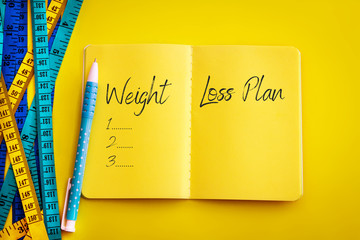"Weight loss and Diet control concept background. Colorful of Measuring tape on vibrant yellow color  background with blue book diary notepad and text as "" Weight Loss Plan ""  for a healthy fitness ."