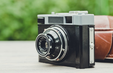 Old film camera on the background of the spring garden. Retro Photo