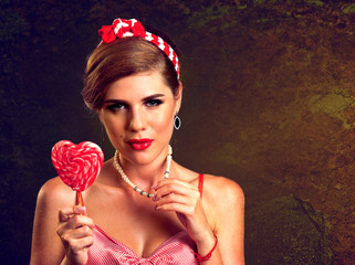 Woman eating lollipops. Girl in pin-up style hold striped candy. Pin up retro female style. Female wearing red dress looking seductively. Girl is confident in her beauty and sexuality.