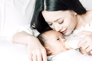 Mother feeding baby from milk bottle
