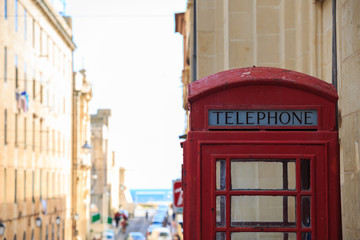 Red British telephone booth. Empty, vintage, peeled phone box in Valletta, Malta. Copyspace, close up view, blurred town background.