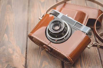 Old film camera on the background of a wooden table