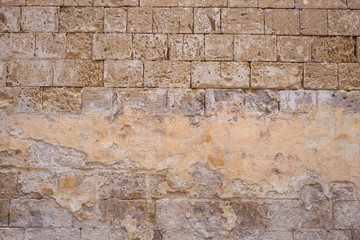 Limestone, sandstone brown, grey background. Aged, peeled, vintage, empty wall for backdrop. Close up view with details.