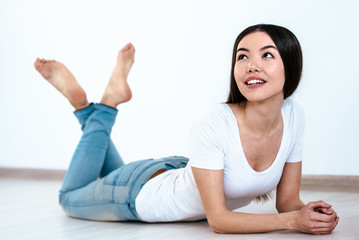 The happy woman laying on the floor on the white background