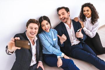 The happy business people making selfie on the floor
