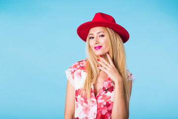 Portrait of smiling blonde woman in fashionable look on blue background. Style, fashion, summer and people concept