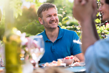 Portrait of a man in a group of friends gathered around a table in a garden on a summer evening to share a meal and have a good time together