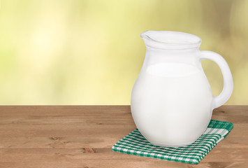 Jug of milk and on napkin on wooden table