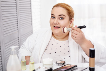 I am beautiful. Cheerful stout woman wearing a bathrobe and applying make-up