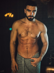 A handsome, muscular man with a beard lies in a bronze bathroom. Steam coming from the hot water. He looks at the camera, drops of water running down the body