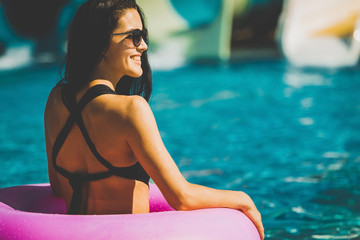 beautiful woman with perfect figure in black swimwear in pink rubber ring in blue swimming pool. Summer Vacation. Enjoying suntan. holidays at resort