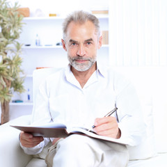 Businessman sitting on the couch and examines important documents