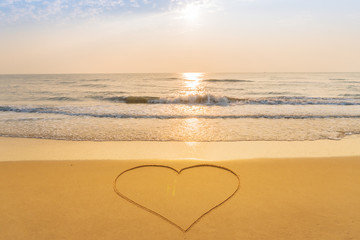 Heart drawn on the sand beach background at sunrised