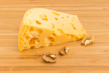 Piece of Swiss cheese and walnuts on bamboo cutting board