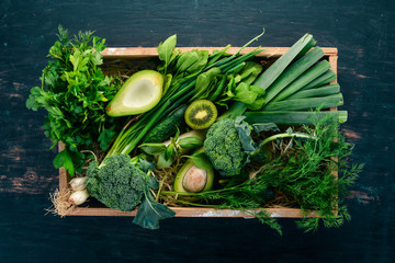 Fresh green vegetables and fruits in a wooden basket. Healthy food. Top view. Copy space.