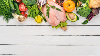 Chicken breast and fresh vegetables. On a white wooden background. Healthy food. Top view. Copy space.