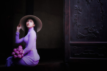 Vietnam woman wearing Ao Dai culture traditional at old temple at Ho Chi Minh in Vietnam,vintage style,travel and relaxing concept.