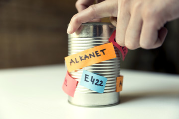 Woman's hand opening canned food with paper notes naming food additives. Healthy food concept