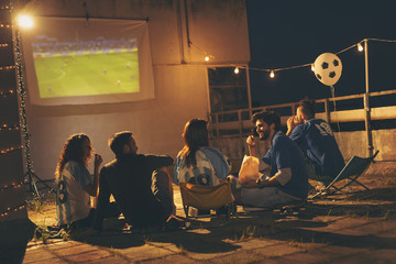 Group of friends watching football on a building rooftop